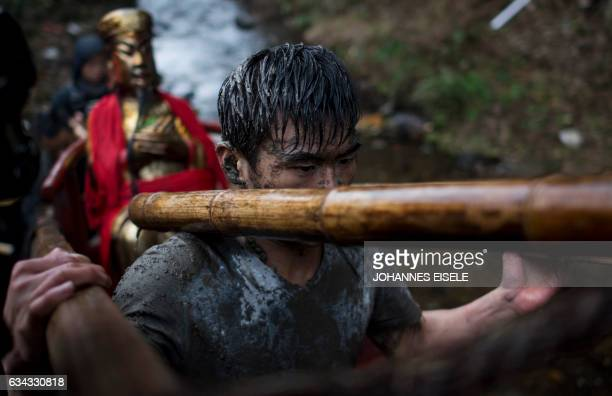 This picture taken on February 8 2017 shows a villager carrying a golden statue of an ancient Chinese general who like Robin Hood is celebrated for...