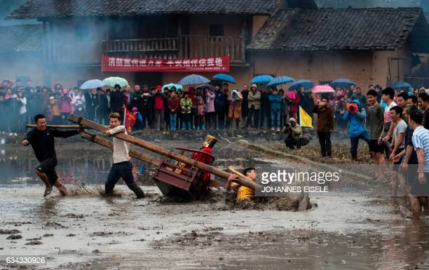 This picture taken on February 8 2017 shows villagers carrying a golden statue of an ancient Chinese general who like Robin Hood is celebrated for...
