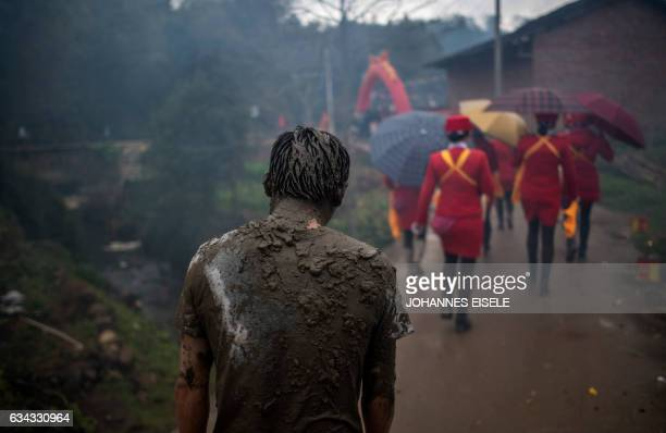 TOPSHOT This picture taken on February 8 2017 shows villagers covered in mud after taking part in a festival in the village of Juhe in China's Fujian...