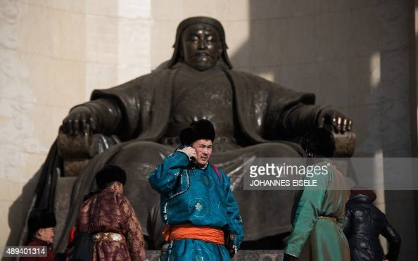 This picture taken on February 9 2015 shows a man standing next to a statue of Genghis Khan in front of the Parliament House on Sukhbaatar Square in...