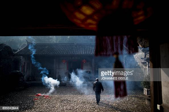 This picture taken on February 9 2017 shows a man setting off fireworks in an ancient compound before a dragon parade in Peitian village Liancheng...