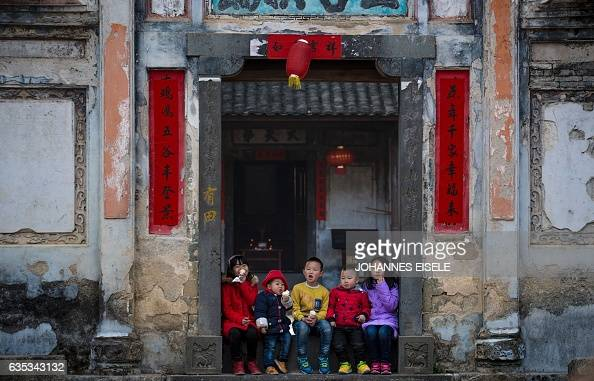 This picture taken on February 9 2017 shows children eating ice cream as they await a dragon parade in Peitian village Liancheng county of China's...