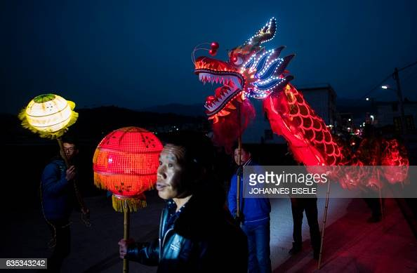 This picture taken on February 9 2017 shows villagers carrying a dragon as they parade through the streets in Peitian village Liancheng county of...