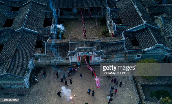 TOPSHOT This picture taken on February 9 2017 shows villagers parading a dragon through an ancient compound in Peitian village Liancheng county of...
