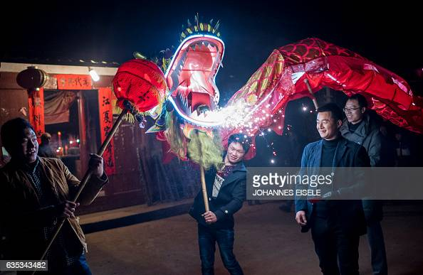 This picture taken on February 9 2017 shows villagers parading a dragon through Peitian village Liancheng county of China's eastern Fujian province...