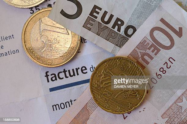 This picture taken on January 01 2013 shows a EDF electricity bill with euros coins on in the western city of Rennes AFP PHOTO / DAMIEN MEYER