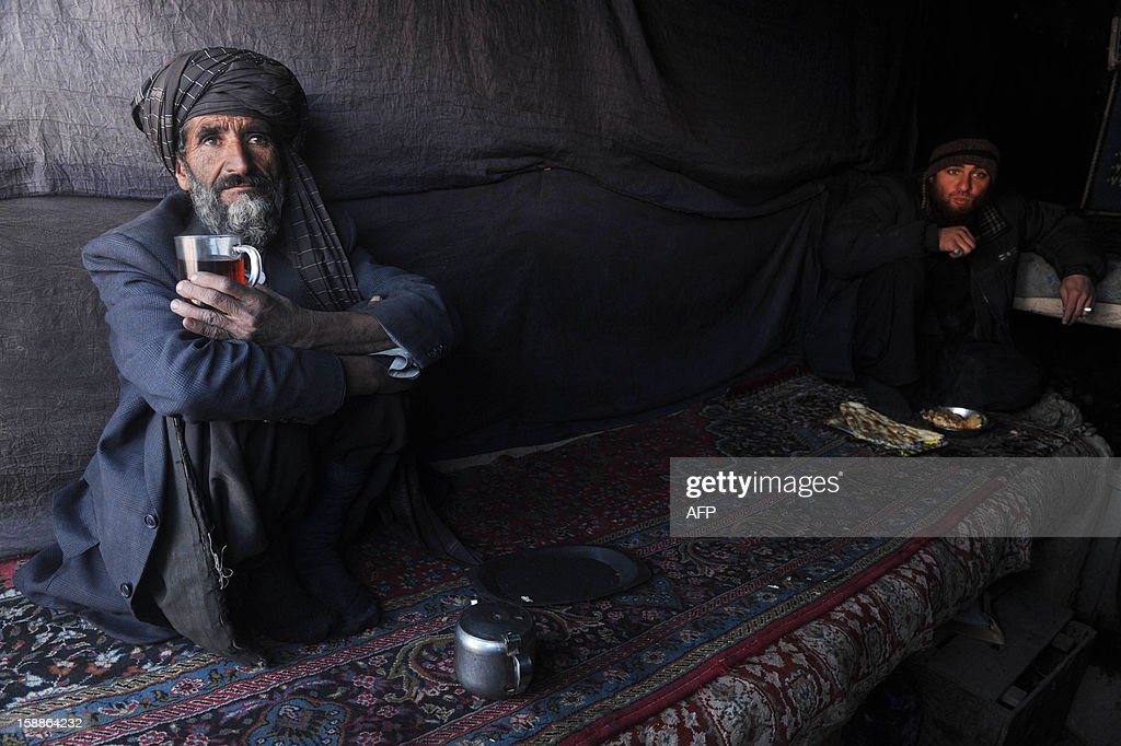 This picture taken on January 1, 2013 shows Afghan customers drinking tea at a local teashop in Herat. The war-torn country still faces poverty, unemployment and lack of infrastructure despite western aid money which has flooded Afghanistan in the 11 years since a US-led invasion toppled the hardline Islamist Taliban regime in the wake of the September 11 attacks on New York and Washington. Civilians are among the hardest hit as the Taliban wage an increasingly bloody insurgency against the government. AFP PHOTO/ Aref Karimi