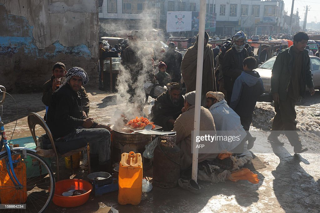 This picture taken on January 1, 2013 shows Afghan customers eating at roadside shops in Herat. The war-torn country still faces poverty, unemployment and lack of infrastructure despite western aid money which has flooded Afghanistan in the 11 years since a US-led invasion toppled the hardline Islamist Taliban regime in the wake of the September 11 attacks on New York and Washington. Civilians are among the hardest hit as the Taliban wage an increasingly bloody insurgency against the government. AFP PHOTO/ Aref Karimi