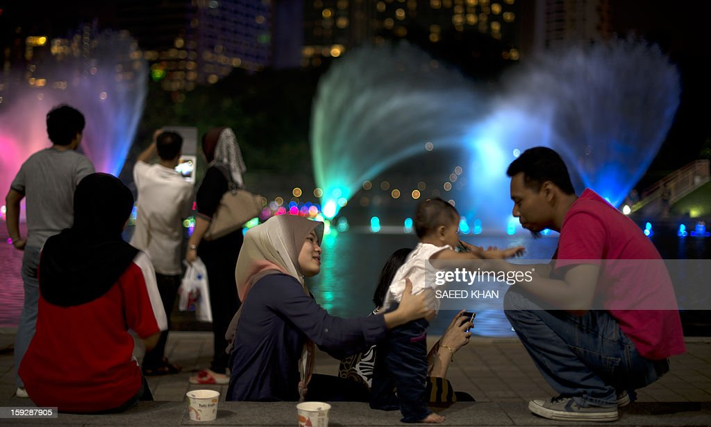 This picture taken on January 10, 2013 shows family members in front of a fountain in the business hub of Kuala Lumpur. Malaysia's economy grew a better-than-expected 5.2 percent in the third quarter as domestic demand compensated for the weakening exports, spurred on by government spending ahead of elections this year. The government has forecast 5.0 percent full-year growth for 2012. AFP PHOTO / Saeed Khan
