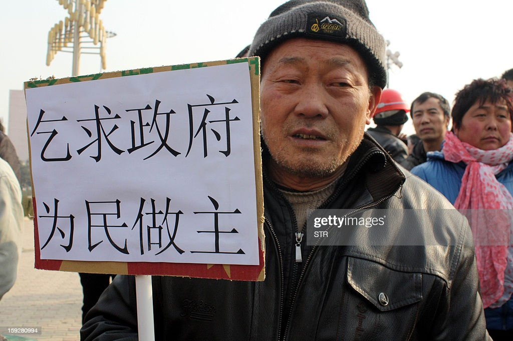 This picture taken on January 10, 2013 shows migrant workers protesting with a placard urging the government assist to retrieve unpaid salary back from their previous employers who are property developers, on a square in Fuping, central China's Shanxi province. The group of more than 2500 migrant workers, mostly from Sichuan province, have been striving to get back their salary, a total of more than 60 million yuan, ever since October, 2012 but has so far ended up in vain after the company refused to pay out. CHINA