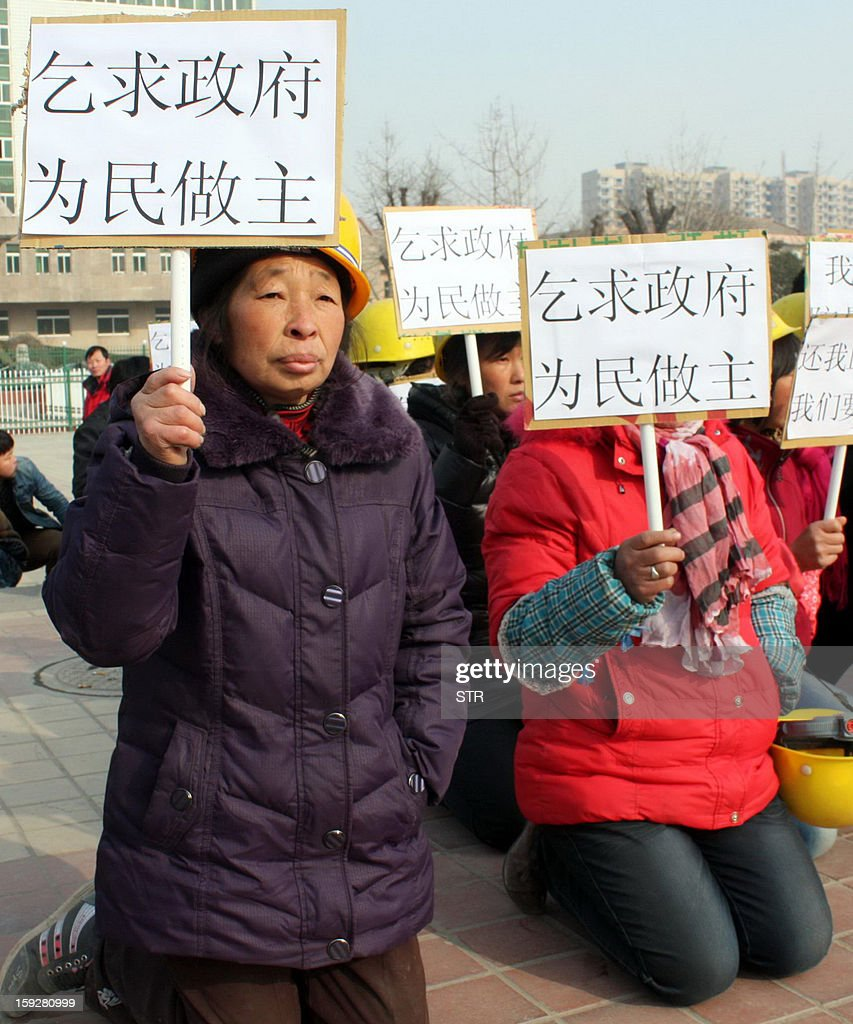 This picture taken on January 10, 2013 shows migrant workers protesting with placards urging the government assist to retrieve unpaid salary back from their previous employers who are property developers, on a square in Fuping, central China's Shanxi province. The group of more than 2500 migrant workers, mostly from Sichuan province, have been striving to get back their salary, a total of more than 60 million yuan, ever since October, 2012 but has so far ended up in vain after the company refused to pay out. CHINA