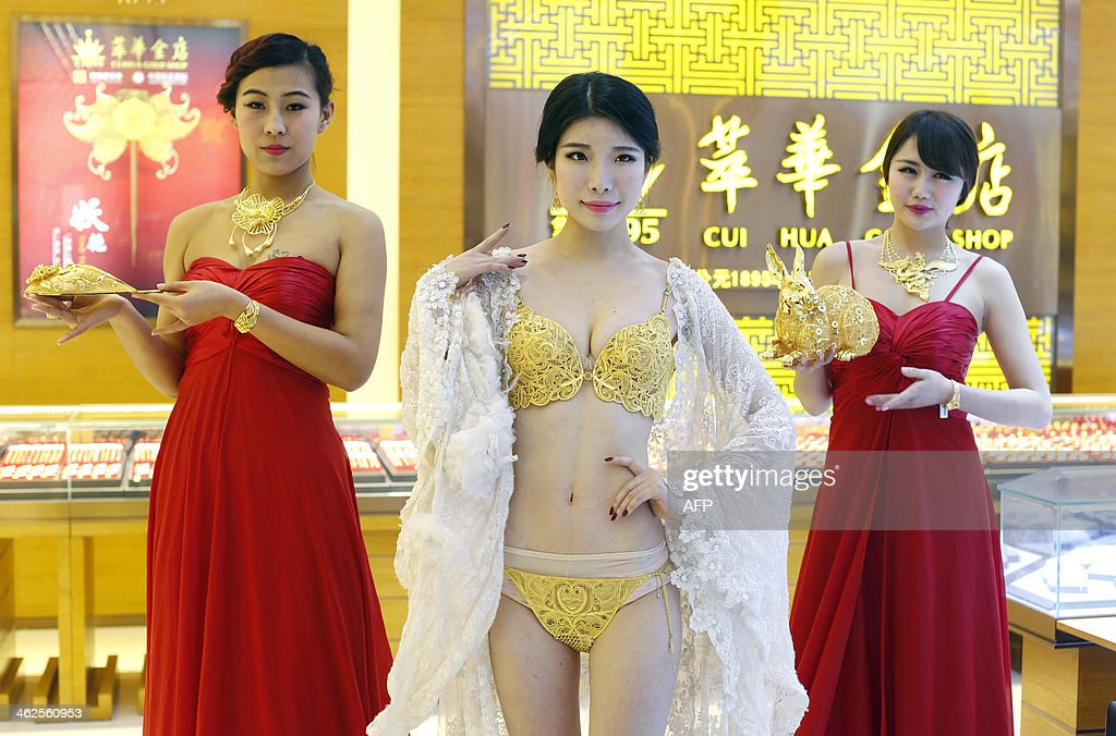 This picture taken on January 11, 2014 shows a model (C) displaying a set of underwear made of gold in a gold shop in Wuhan, central China's Hubei province. The garments are made up of about five million yuan's worth of gold, according to China News. The unnamed woman was joined by two other models - both of whom posed with glittering gold accessories, including necklaces, a shoe and a rabbit. CHINA