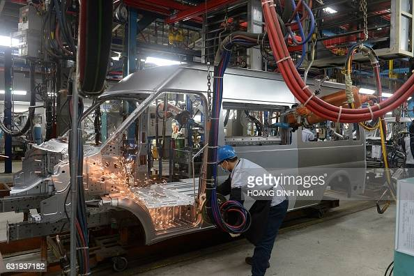 This picture taken on January 11 2017 shows a Vietnamese employee welding in the body shop at the Ford automotive plant in the northern province of...