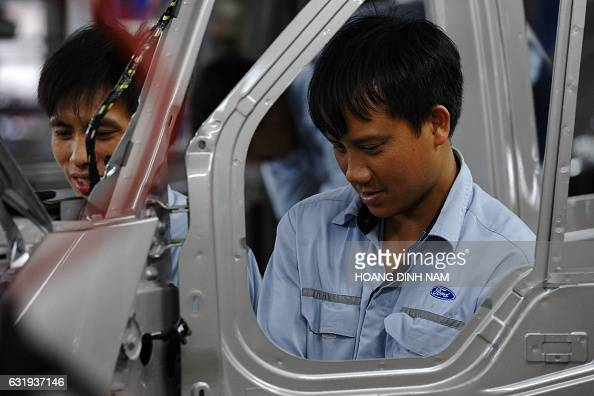 This picture taken on January 11 2017 shows a Vietnamese employees on the assembly line at the Ford automotive plant in the northern province of Hai...