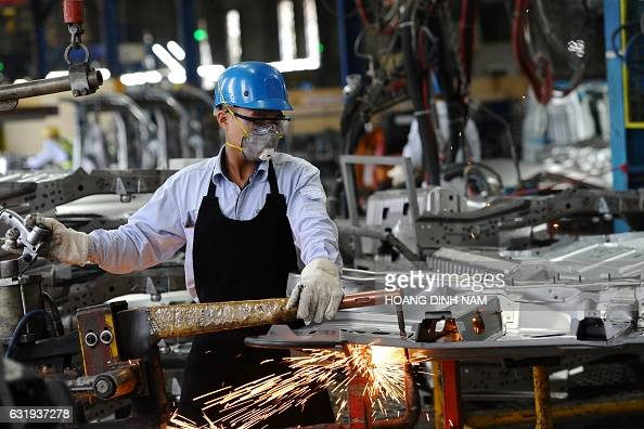 This picture taken on January 11 2017 shows a Vietnamese worker welding in the body shop at the Ford automotive plant in the northern province of Hai...