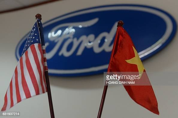This picture taken on January 11 2017 shows US and Vietnamese flags on the front desk at the Ford automotive plant in the northern province of Hai...