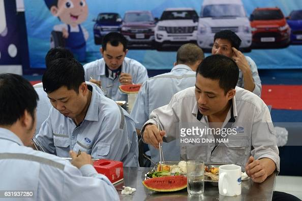 This picture taken on January 11 2017 shows Vietnamese employees eating lunch at the Ford automotive plant in the northern province of Hai Duong...