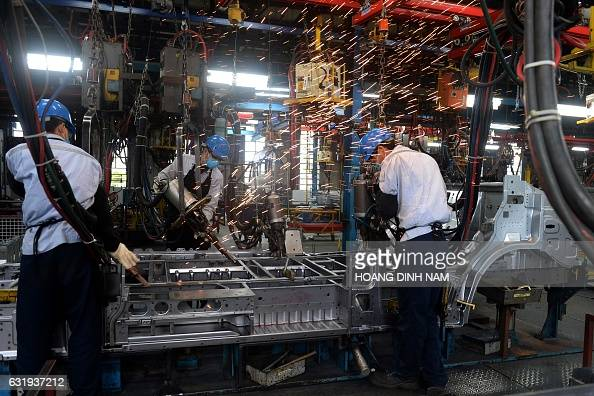 This picture taken on January 11 2017 shows Vietnamese employees welding in the body shop at the Ford automotive plant in the northern province of...