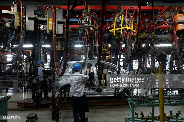 This picture taken on January 11 2017 shows Vietnamese employees working in the body shop at the Ford automotive plant in the northern province of...