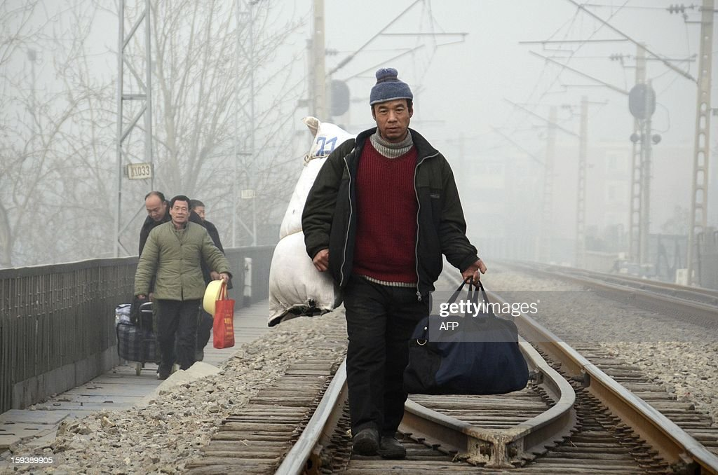 This picture taken on January 12, 2013 shows a Chinese migrant worker walking with his baggage along a railway line in Beijing. China's economy is poised finally to end a long downward trend in 2013, economists polled by AFP say, as the new communist leadership vows to retool the nation's investment-led development model and promote a 'happy life' for all.