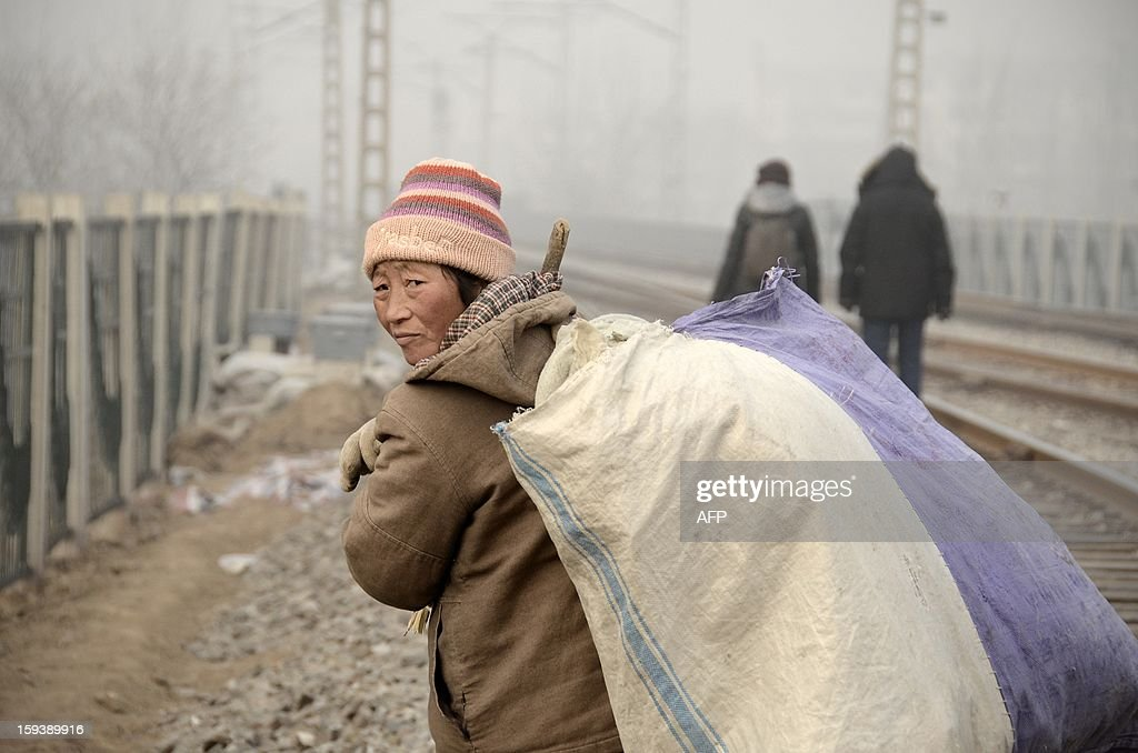 This picture taken on January 12, 2013 shows a Chinese woman walking with her baggage on her back along a railway line in Beijing. China's economy is poised finally to end a long downward trend in 2013, economists polled by AFP say, as the new communist leadership vows to retool the nation's investment-led development model and promote a 'happy life' for all.