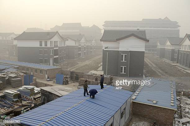 This picture taken on January 12 2013 shows a group of Chinese workers doing their jobs on the roof of a house in Beijing China's economy is poised...