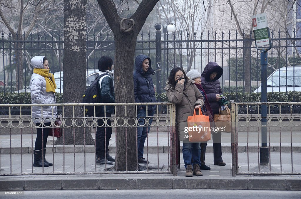 This picture taken on January 12, 2013 shows people waiting the bus at a bus station in Beijing. Mask-wearing Beijing residents endured a third day of pollution at hazardous levels on January 13, as authorities warned that a thick cloud of smog may not lift from the Chinese capital until midweek.