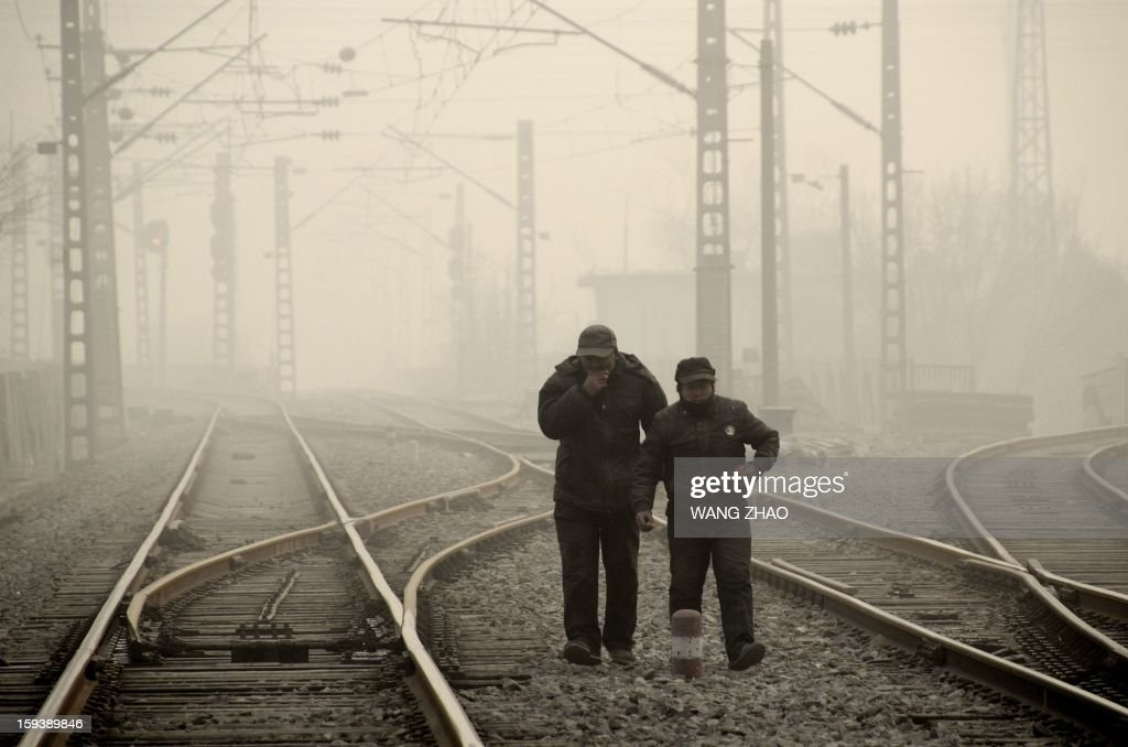 This picture taken on January 12, 2013 shows two Chinese men walking along a railway line in Beijing. Dense smog shrouded Beijing on January 12, with pollution at hazardous levels for a second day and residents advised to stay indoors, state media said.