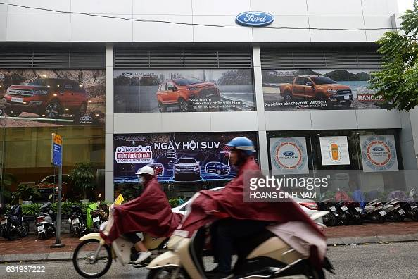 This picture taken on January 12 2017 shows motorcyclists riding past a Ford showroom in downtown Hanoi Vietnam now boasts one of Southeast Asia's...