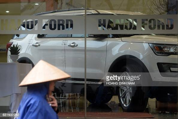 This picture taken on January 12 2017 shows woman walking past a Ford showroom in downtown Hanoi Vietnam now boasts one of Southeast Asia's fastest...