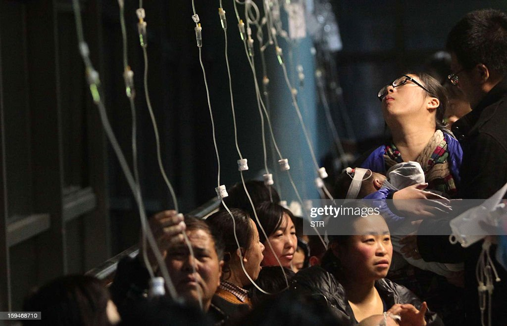 This picture taken on January 13, 2013 shows a row of intravenous drips for parents taking their kids to hospital for flu treatment in Beijing. Public anger in China at dangerous levels of air pollution, which blanketed Beijing in acrid smog, spread on January 14 as state media editorials queried official transparency and the nation's breakneck development. CHINA