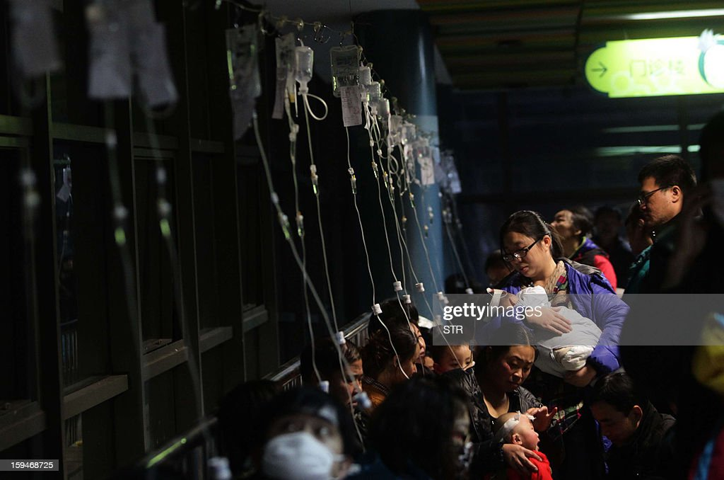This picture taken on January 13, 2013 shows a row of intravenous drips for parents taking their kids to hospital for flu treatment in Beijing. Public anger in China at dangerous levels of air pollution, which blanketed Beijing in acrid smog, spread on January 14 as state media editorials queried official transparency and the nation's breakneck development. CHINA OUT AFP PHOTO