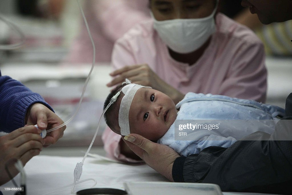 This picture taken on January 13, 2013 shows nurses attending to a baby (C) in hospital for flu treatment in Beijing. Public anger in China at dangerous levels of air pollution, which blanketed Beijing in acrid smog, spread on January 14 as state media editorials queried official transparency and the nation's breakneck development. CHINA