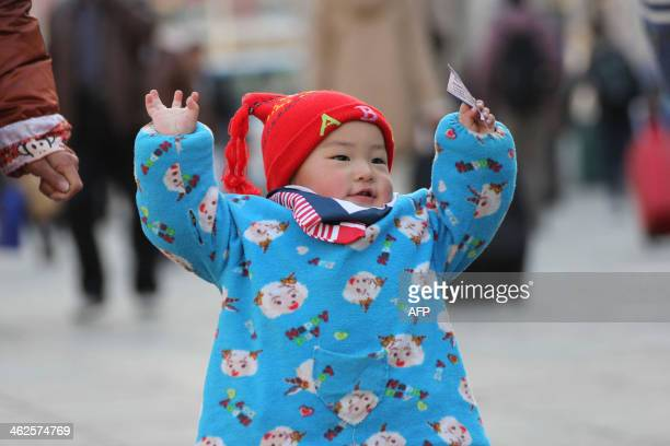 This picture taken on January 13 2014 shows a kid holding a train ticket in Qingdao train station in Qingdao east China's Shandong province A total...