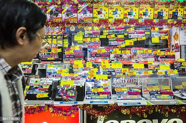 This picture taken on January 13 2017 shows a man walking past a retailer selling new laptop computers in an electronics shop in the Sham Shui Po...