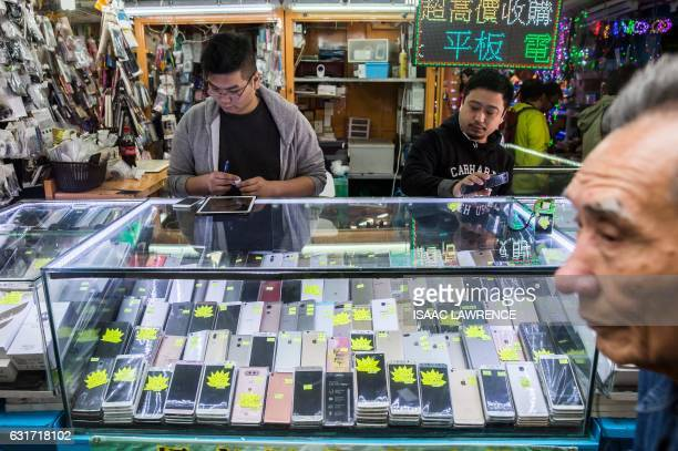 This picture taken on January 13 2017 shows workers in a secondhand mobile phone store in the Sham Shui Po district of Hong Kong Electronic waste is...