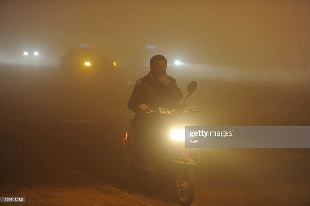 This picture taken on January 14, 2013 shows a man covering his mouth with his hand as he rides in heavy fog in Hefei, central China's Anhui province. Shares in a Chinese face mask manufacturer soared on January 15 as investors looked for opportunities to cash in on the severe air pollution that has blanketed large swathes of China. CHINA