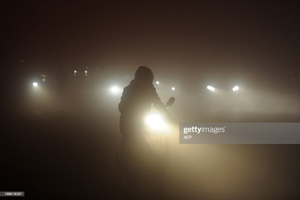 This picture taken on January 14, 2013 shows a man riding in heavy fog in Hefei, central China's Anhui province. Shares in a Chinese face mask manufacturer soared on January 15 as investors looked for opportunities to cash in on the severe air pollution that has blanketed large swathes of China. CHINA OUT AFP PHOTO