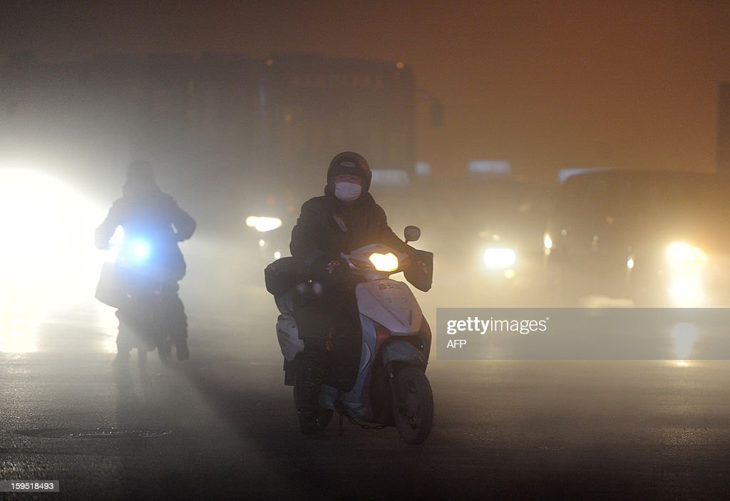 This picture taken on January 14, 2013 shows a man wear ing a mask as he rides in heavy fog in Hefei, central China's Anhui province. Shares in a Chinese face mask manufacturer soared on January 15 as investors looked for opportunities to cash in on the severe air pollution that has blanketed large swathes of China. CHINA OUT AFP PHOTO