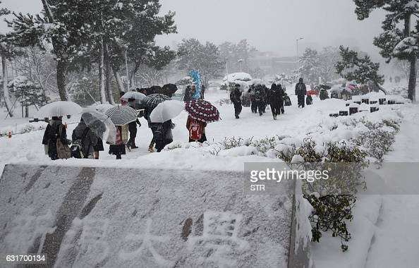 This picture taken on January 14 2016 shows students heading to a venue for college entrance examinations under falling snow in Niigata The Japan...