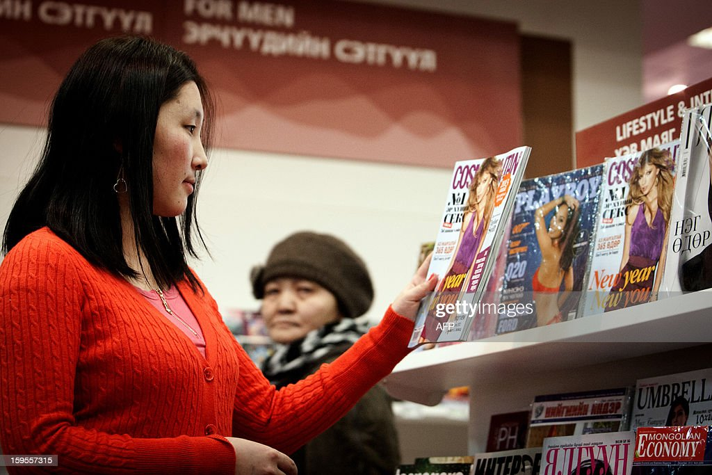 This picture taken on January 15, 2013 shows a Mongolian woman browsing various magazines at a bookstore, including Cosmopolitan which was launched in December 2010 and has built a circulation of 5,000 copies, in Ulan Bator. Every time a new Mongolian-language edition of Cosmopolitan magazine is released, Tselmeg Erdenkhuu sits down with a friend to explore a monthly dose of Hollywood gossip, glitzy fashion and scintillating sex.