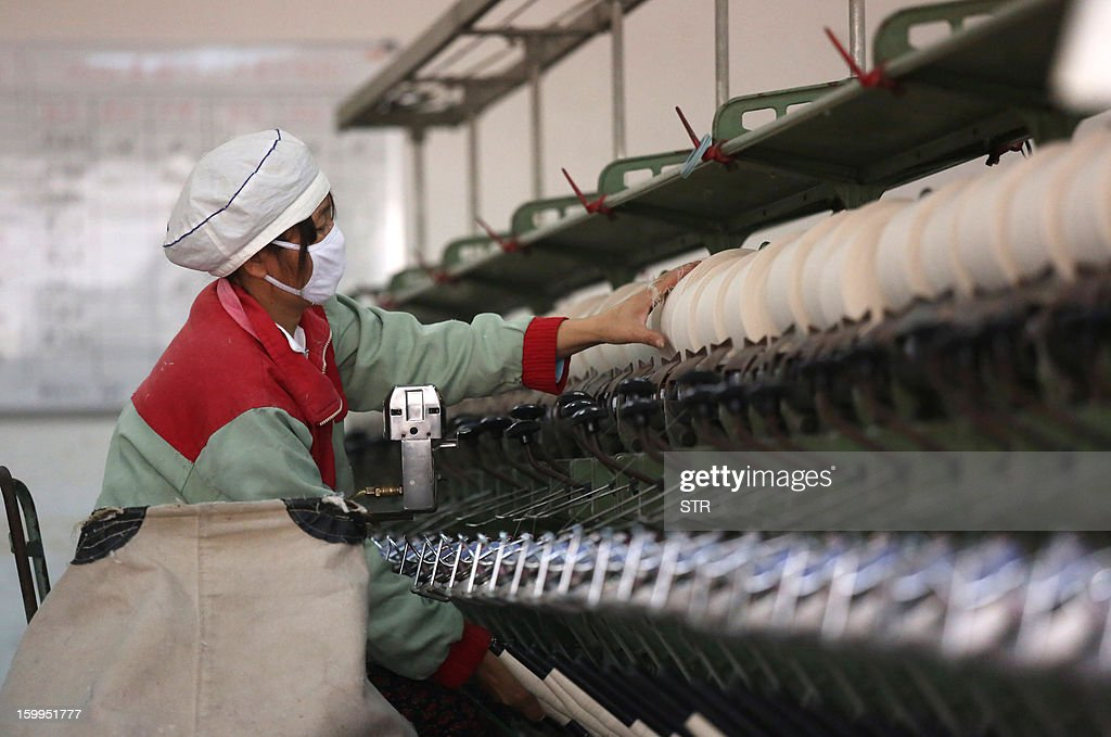 This picture taken on January 16, 2013 shows a woman working in a textile factory in Jiujiang, east China's Jiangxi province. China's manufacturing activity expanded in January at its fastest pace in two years, HSBC said on January 24, the latest sign of recovery in the world's second biggest economy. CHINA OUT AFP PHOTO