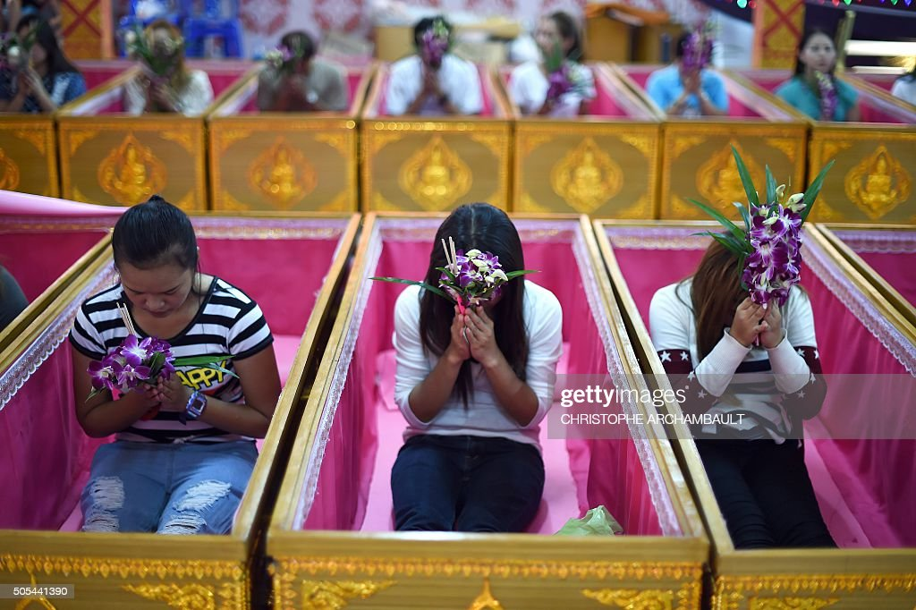 This picture taken on January 16 2016 shows devotees offering prayers as they sit in coffins at the end of a group resurrection ceremony at the Wat...