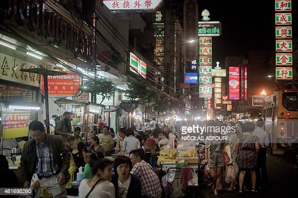 This picture taken on January 16 shows people eating at food stalls and walking along a street in the Chinatown area of Bangkok Thailand's economy...