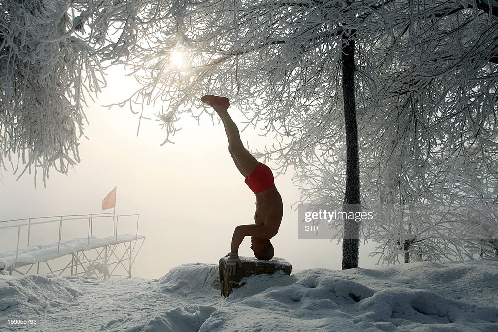 This picture taken on January 17, 2013 shows 77-year-old retired teacher Gao Yinyu exercising in his underwear at a snow-covered bathing spot in Jilin, in northeastern China's Jilin province, in a temperature of minus 25 degrees Celsius. Gao has been exercising in only his underwear every morning for more than the past decade and has rarely caught cold ever since retirement. CHINA OUT AFP PHOTO
