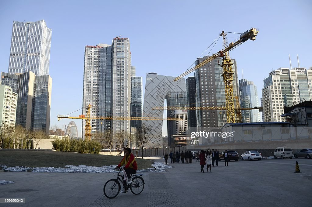 This picture taken on January 17, 2013 shows a Chinese man riding a bicycle past a construction site in a central business district in Beijing. China's economy grew at its slowest pace in 13 years in 2012, the government said on January 18, but an uptick in the final quarter pointed to better news ahead for a prime driver of the tepid global recovery.