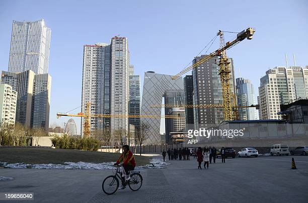 This picture taken on January 17 2013 shows a Chinese man riding a bicycle past a construction site in a central business district in Beijing China's...