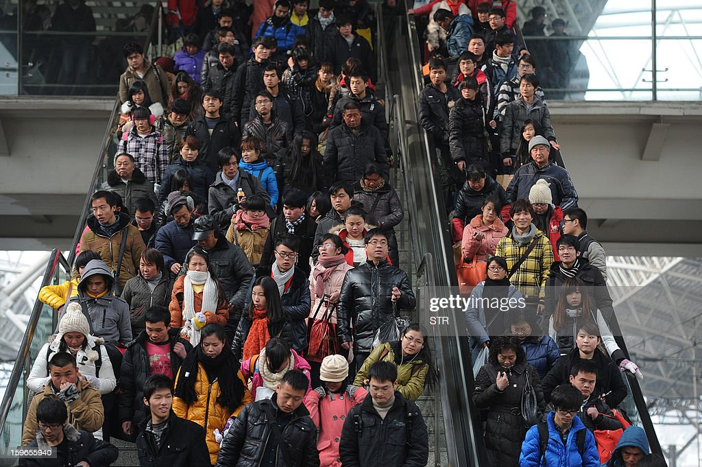 This picture taken on January 17, 2013 shows people riding an escalator, headed for their trains at a railway station in Hefei, in central China's Anhui province. China's working-age population declined for the first time in recent decades in 2012, the government said on January 18, as it detailed the extent of the demographic time bomb the country faces. CHINA