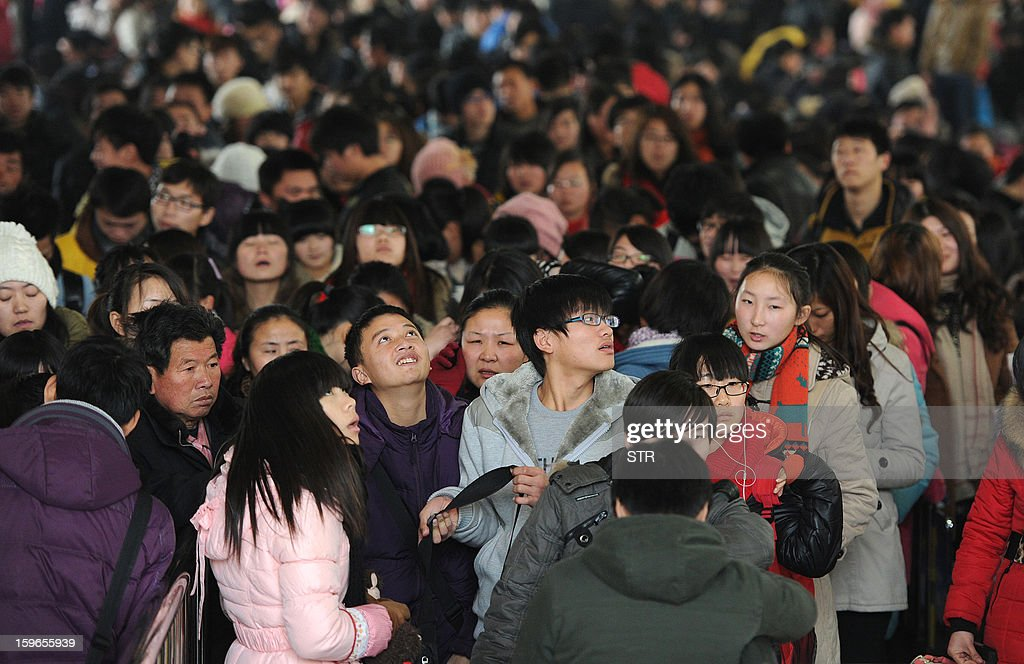 This picture taken on January 17, 2013 shows people waiting at a railway station in Hefei, in central China's Anhui province. China's working-age population declined for the first time in recent decades in 2012, the government said on January 18, as it detailed the extent of the demographic time bomb the country faces. CHINA OUT AFP PHOTO