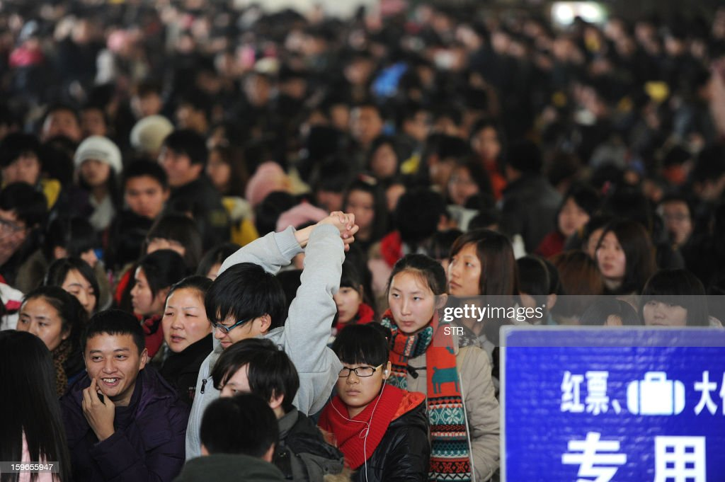 This picture taken on January 17, 2013 shows people waiting at a railway station in Hefei, in central China's Anhui province. China's working-age population declined for the first time in recent decades in 2012, the government said on January 18, as it detailed the extent of the demographic time bomb the country faces. CHINA